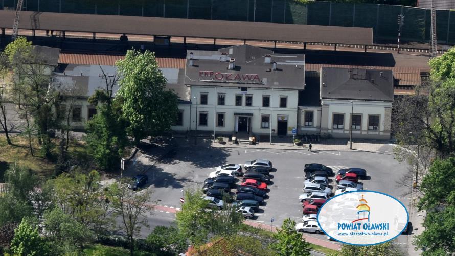 Stacja kolejowa PKP w Oławie oraz parking przed obiektem.