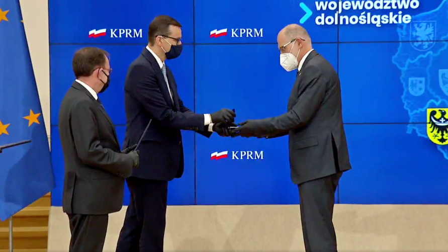 Na zdjęciu widzimy trzech mężczyzn. Premier wręcza staroście odznaczenie.