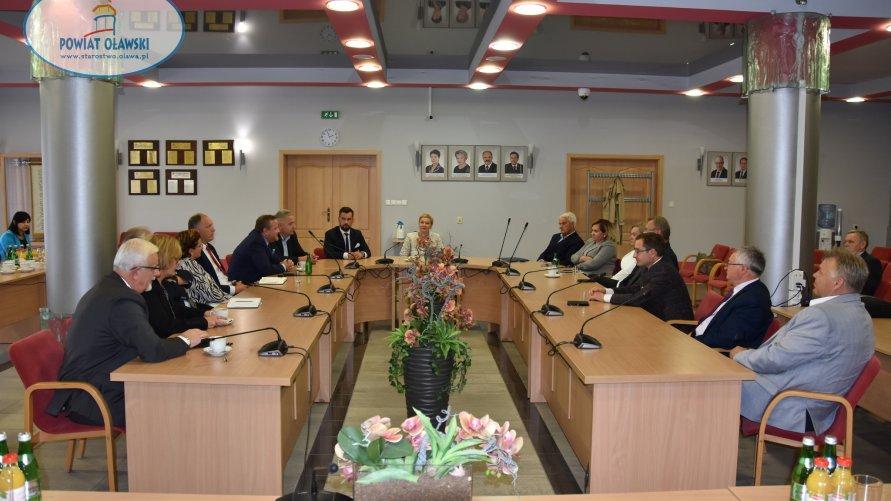 Sala konferencyjna. Przy stole siedzą samorządowcy.