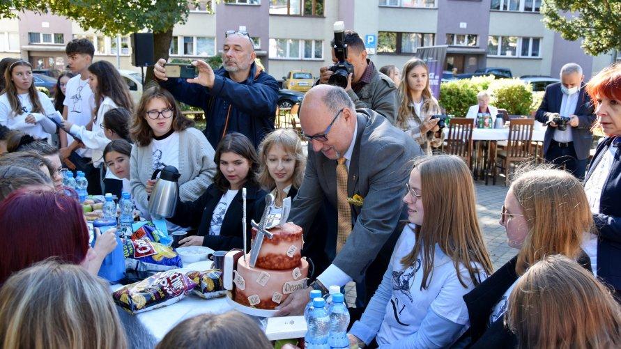 Na zdjęciu widzimy stół pełen słodkości. Przy stole siedzą młodzi uczniowie. Do nich nachyla się wicestarosta z tortem.