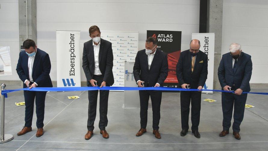 Przedstawiciele firmy Eberspächer oraz zaproszeni samorządowcy przecinają wstęgę podczas otwarcia nowej hali produkcyjnej nr 3 w Godzikowicach.