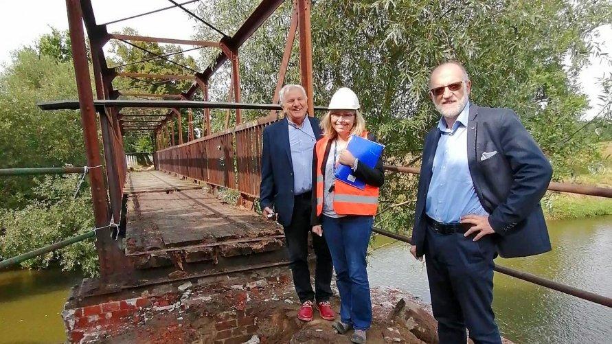 Na zdjęciu widzimy przeprawę mostową nad Odrą, po prawej stronie stoją trzy osoby.