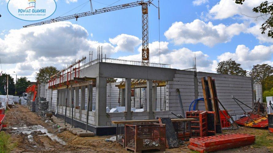Plac budowy. Widać ściany parteru obiektu, nad nimi dźwig.