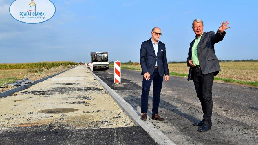 Na pierwszym planie widzimy dwóch mężczyzn. Jeden wskazuje coś ręką, drugi przygląda się. W tle inwestycja drogowa.