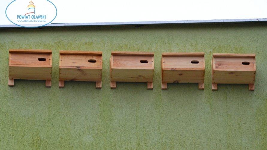 Na fot widzimy elewacje budynku, na której zamontowano budki lęgowe dla ptaków